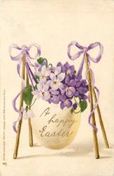 A HAPPY EASTER  egg containing bunch of violets slung by violet ribbons on sticks as a swing