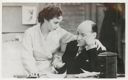 Jessie Matthews confers with seated man
