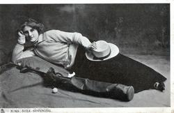MISS NINA SEVENING in golf attire lying  with bag of clubs & ball at her side
