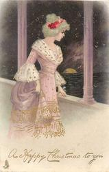 A HAPPY CHRISTMAS TO YOU  girl in violet dress, stands on balcony looking out at sea