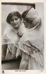 MISS JEAN AYLWIN  in lace scarf, looks in large mirror