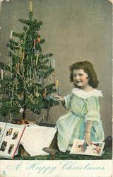 A HAPPY CHRISTMAS  small girl kneeling by Christmas tree