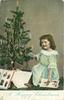 A HAPPY CHRISTMAS  small girl kneeling by Christmas tree