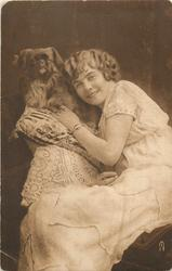 young lady sits looking forward facing left, left hand supports pekingese dog sitting up by her face