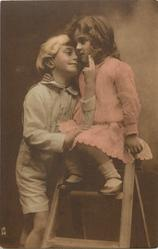 young children & wooden step-ladder, boy stands left with eyes closed, hand on her knee, girl sits on top of step-ladder, faces close