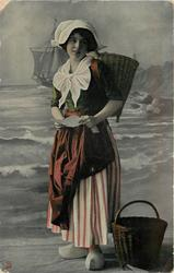 Dutch girl looks down at letter held with both hands, striped skirt, bl/w  background of coast & sailing ship