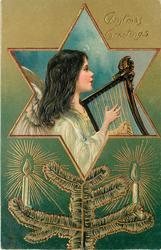 CHRISTMAS GREETINGS angels plays harp in star inset, evergreen below