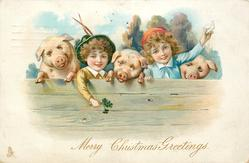 A MERRY CHRISTMAS  boy holding lucky clover, girl holding up a letter & thee pigs all line up behind a wooden fence