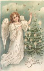 CHRISTMAS GREETINGS angel, left, admires Xmas tree, right