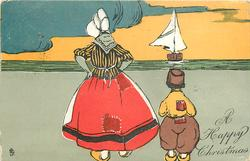 A HAPPY CHRISTMAS, woman and boy standing, all in yellow clogs, sailboat and ocean back