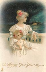 girl stands in front of mother sitting in white dresses on balcony seascape behind