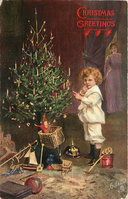 child in boots stands beside Christmas tree, toys on the ground