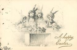 four girls in bunny costumes stand behind wall looking down on four chicks on top of pen
