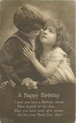 A HAPPY BIRTHDAY boy in sailor suit kisses cheek of girl, her left arm is on his chest