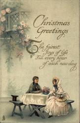 CHRISTMAS GREETINGS couple in old style dress sit facing each ohter across table below window & roses