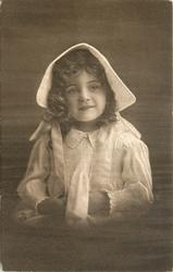 young girl in bonnet & dress sits facing & looking front, hands touching together under tie