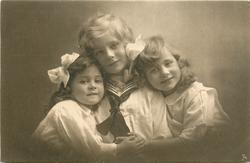 boy in sailor suit between two girls, both girls have hands high on boys chest well below the knot on his tie, anchor shows on boys shirt, boy looks front