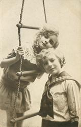 boy stands in front of rope ladder, girl behind with head touching his, her head is between middle and upper rung, both are on the right side of the ladder