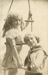 boy stands in front of rope ladder resting his head on the rung, girl behind holding his hand and holding rope, her head is between middle and upper rung