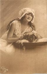 girl with frilly cap left of pekingese dog on pillow which faces front, girl looks up to right
