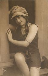 girl in bathing suit  & cap sits in door of bathing hut, she holds her hat on with right hand