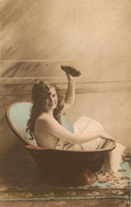 girl sitting in portable bathtub holds up sponge
