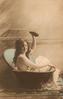 girl sitting in portable bathtub holds up sponge