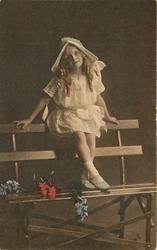 girl in lacy dress & bonnet sits on top ofslatted wooden bench strewn with flowers, legs crossed at ankles