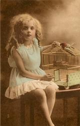 girl sits on table to right of bird cage with stuffed bird perched on top, her left hand rests on top of cage