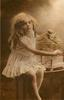 girl sits on table to right of bird cage with stuffed bird perched on top, her right arm reaches across birdcage