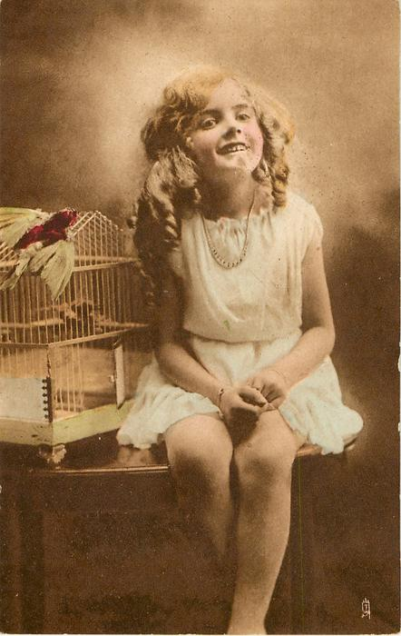 girl sits on table to right of bird cage with stuffed bird perched on top, hands in her lap