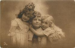 two girls around boy in the middle, girl on the right is hugging boy