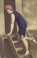 girl in bathing suit & cap stands on steps of front of bathing hut, her left hand holds top of step, right hand hidden, half-kneeling