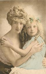 mother holds child in arms,mother to left, heads touch, girls left hand on mothers right shoulder, mothers left hand on childs waist, mothers right hand just under childs left shoulder