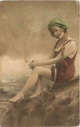 girl in bathing suit & hat sits on rocks, knees together, hands on knees, braid hangs on her left, faces left & looks forward