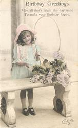 BIRTHDAY GREETINGS girl stands behind bench, holding handle of very large basket filled with flowers
