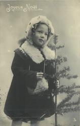 young girl dressed for winter with fur cap, cape & muff, stands facing slightly right, holds tree with left hand on her left side