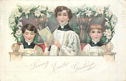 2 boys & a girl chorister sing holding white pages in front of two columns