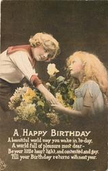 A HAPPY BIRTHDAY boy leans over floral bouquet and holds girl's hand