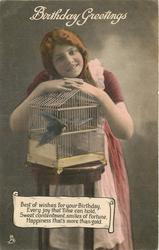 BIRTHDAY GREETINGS girl stands behind bird cage, one bird inside, one bird outside cage