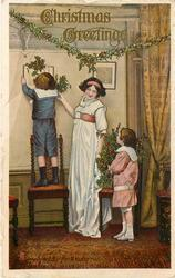 CHRISTMAS GREETINGS boy stands on chair adjusting holly, mother and sister stand right