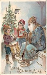 LOVING CHRISTMAS WISHES  blue robed Santa sits on bench rignt, boy with drum & girl reads standing left