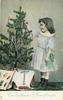 CHRISTMAS GREETINGS girl stands facing left, putting ornament on Xmas tree