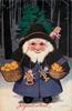 Santa wearing indigo coat in woods facing front looking front with toys around his neck and basket of  fruit under each arm