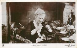 CICELY COURTNEIDGE  sits by table holding spectacles with both hands, looks front & down