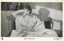 JESSIE MATTHEWS sits in bed her right hand behind her head, facing front looking left
