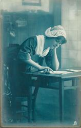 girl in Dutch costume, kneeling at writing table, looking down