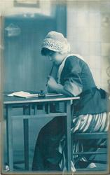 girl in Dutch costume, seated at writing table facing left, pen in left hand and mouth