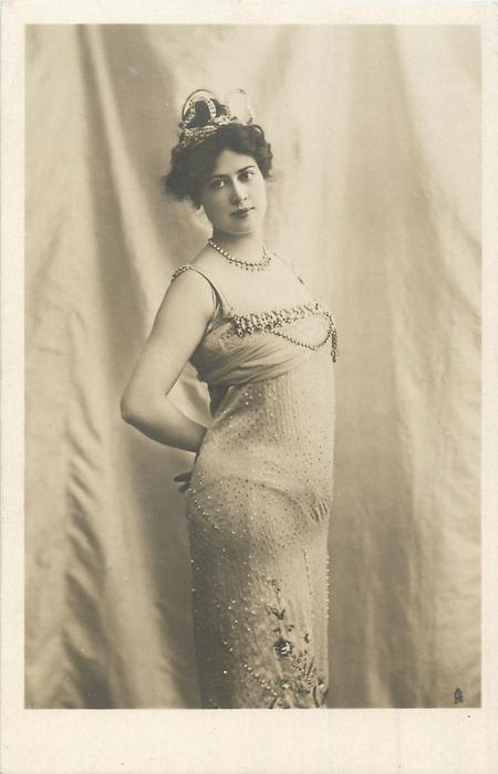 woman posed before curtain in white dress, coronet on peaked up hair, hands behind back, facing right looking front