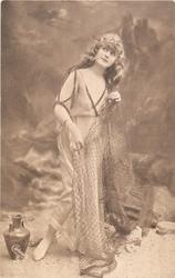 girl in robe stands posed against beach background, she faces forward right, looking up, holding net with both hands, jug on ground to left